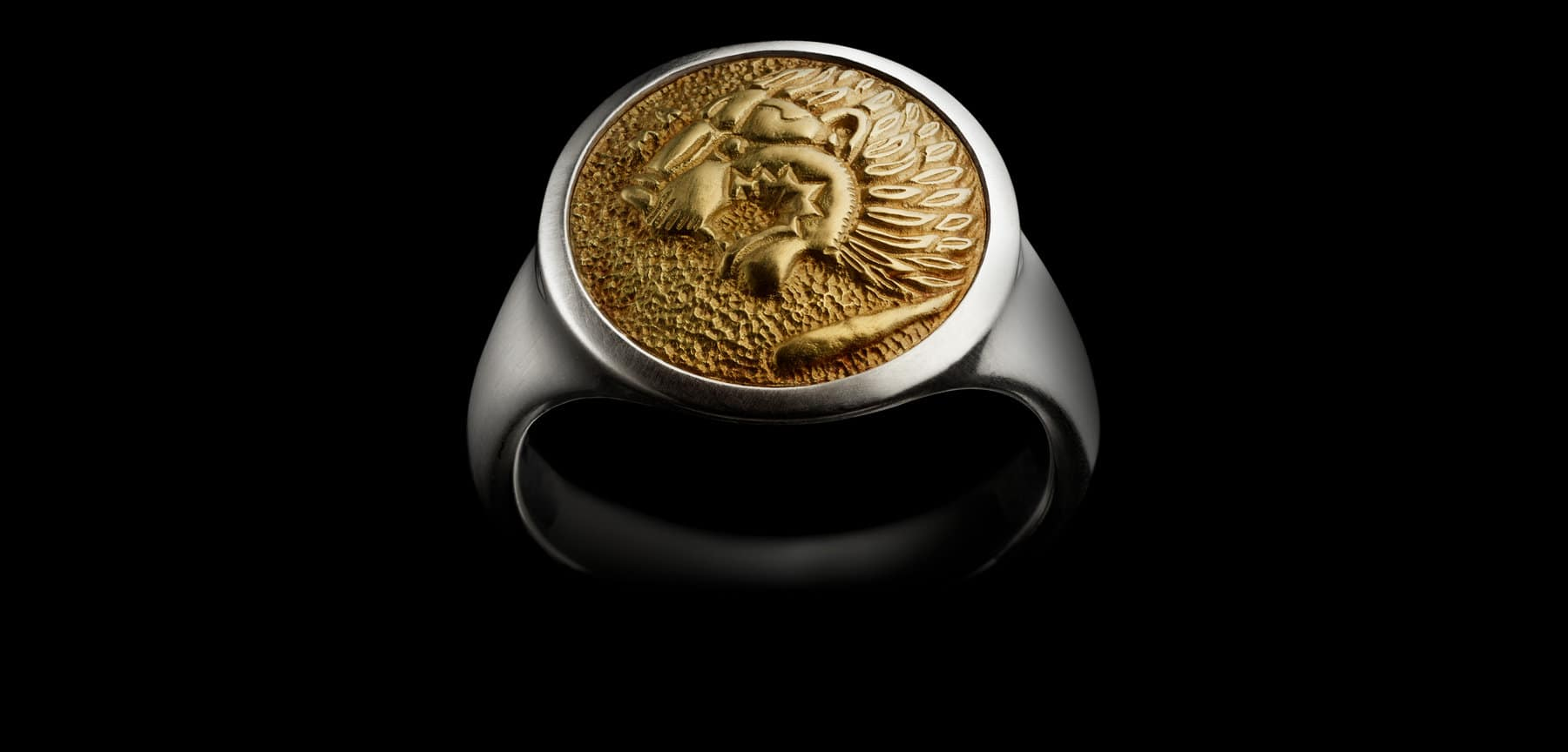 A color photograph shows a David Yurman men's Petrvs® signet ring, crafted from sterling silver with an 18K yellow gold lion emblem, against a black background.