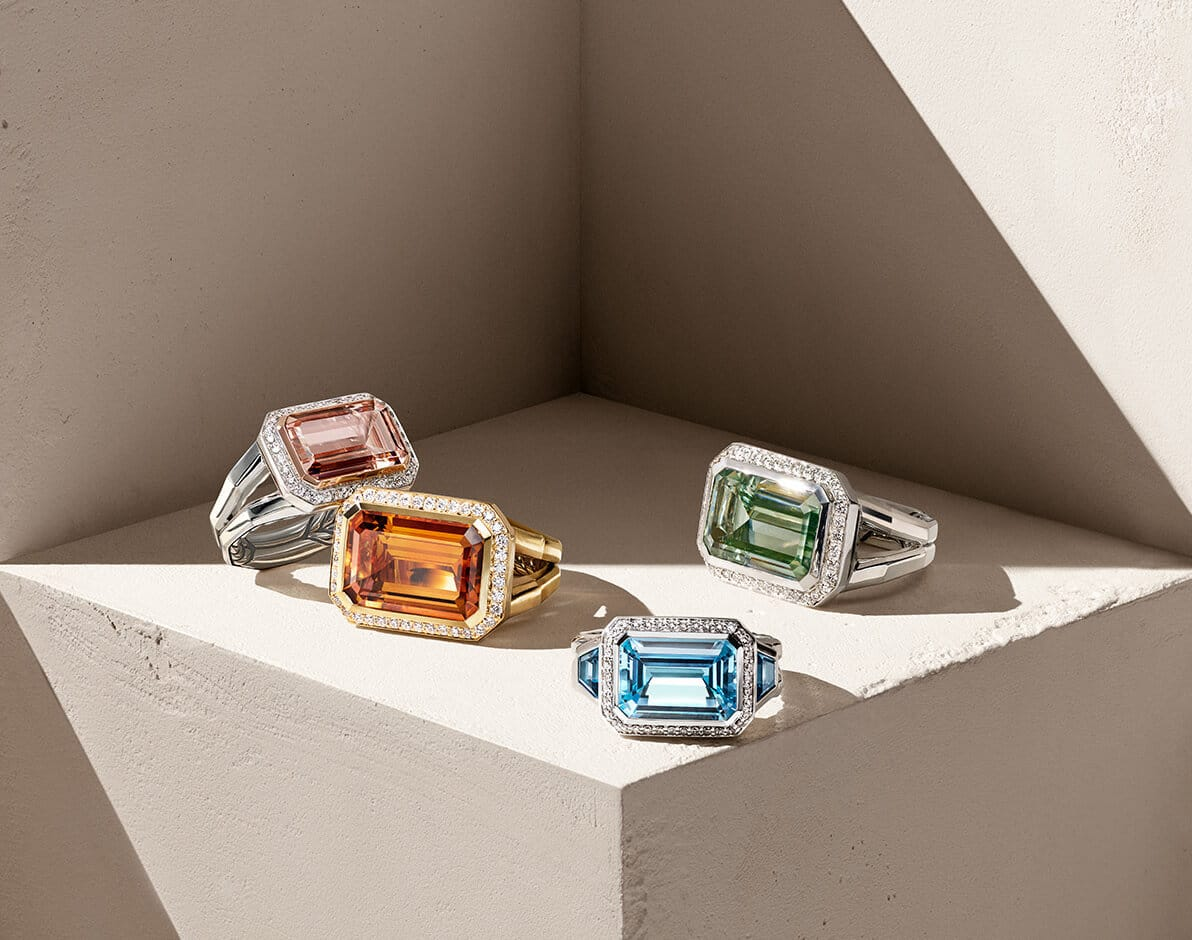 A color photo shows four David Yurman women's Novella rings with pavé diamond bezels arranged on top of a beige stone cube that's covered in light and shadow. From left is a sterling silver ring with a morganite center stone, an 18K yellow gold ring with a Madeira citrine center stone, a sterling silver ring with blue topaz stones and a sterling silver ring with a prasiolite center stone.