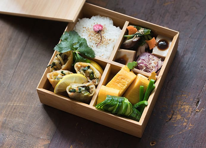 An image of light-brown wooden bento box, with four compartments filled with rice, vegetables, spring rolls and other foods, open on a dark, textured wood surface.