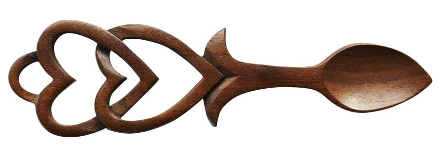 An image of a dark wood lovespoon with interlocking heart motifs at the handle.