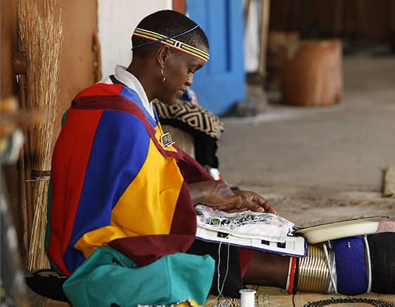 An image of a Zulu woman wearing a colorful garment while sitting on a stone street and creating an intricately beaded object.