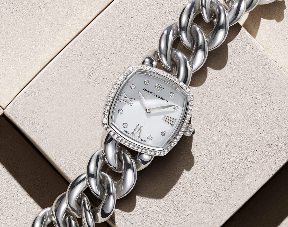A color photograph shows a David Yurman women's bracelet watch placed atop a beige stone surface with graphic shadows. The watch is crafted from stainless steel, and features a pavé diamond bezel and hour markers.