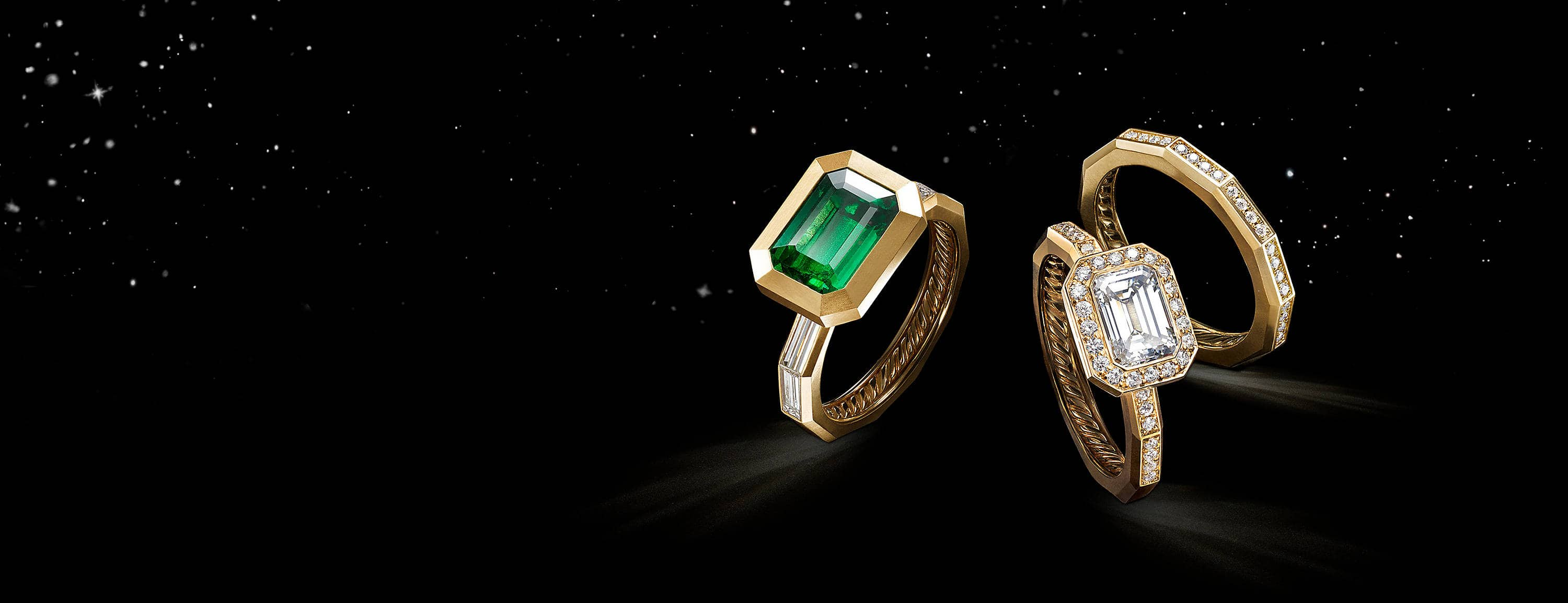 A color photo shows two David Yurman women's engagement rings next to a wedding band floating in front of a starry night sky. The jewelry is crafted from 18K yellow gold with or without an emerald or diamonds.