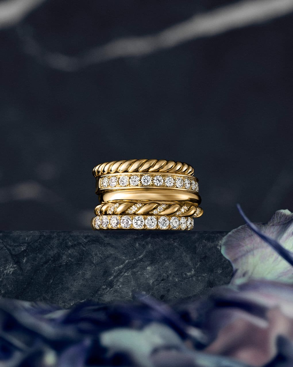 A color photograph shows a stack of five 18K yellow gold wedding bands with or without diamonds from the DY Unity and DY Eden collection. The stack of rings sits atop a dark, marbled stone surface with a dark background and purple flowers in the foreground.