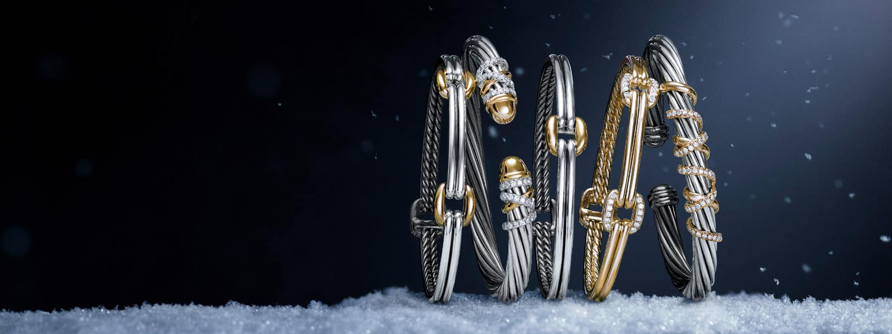 A color photo shows a horizontal stack of five David Yurman bracelets for women from the Thoroughbred and Helena collections leaning against each other. Four women's bracelets are crafted from sterling silver with 18K yellow gold cushion links, pavé-white-diamond-encrusted threads or bonded domes. One women's bracelet is crafted from 18K yellow gold with cushion links encrusted with pavé white diamonds. The jewelry is shot on a stone surface covered with snow at night.