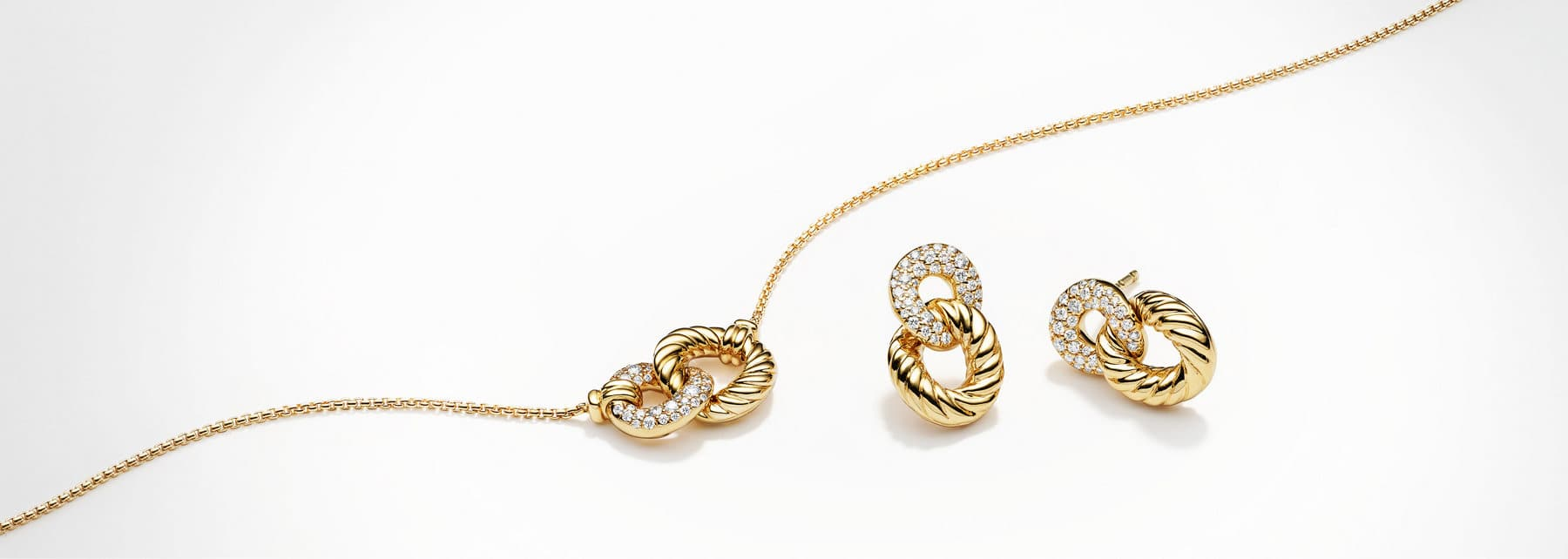 A color photo shows three Belmont curb-chain bracelets in a row in sterling silver and 18k yellow gold, 18K yellow gold or sterling silver atop an off-white background with prominent shadows.