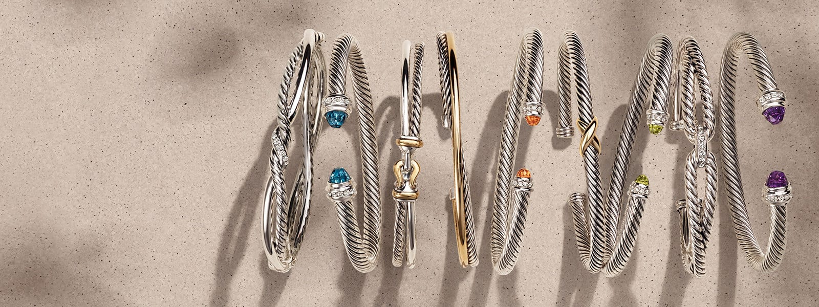 A horizontal stack of David Yurman The Cable Collection®, X Collection and Cable Loop bracelets in sterling silver with or without diamonds, 14K yellow gold or colored gemstones on a beige textured stone with long shadows.