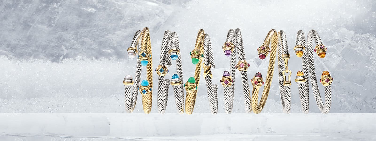 The Cable Collection® bracelets in sterling silver and 18K yellow gold with several colorful gemstones, in a row on sheets of ice.