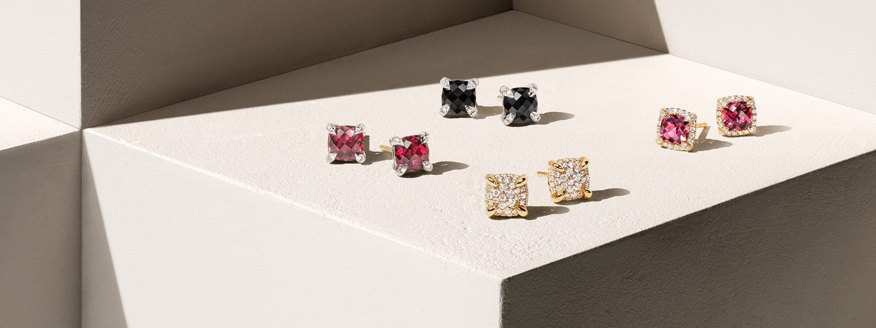 "A color photograph shows four pairs of David Yurman Châtelaine stud earrings for women atop a beige-hued stone shelf with hard shadows. The women's earrings are crafted from 18K yellow gold or sterling silver with garnet or black onyx and pavé diamond-encrusted bezels, prongs or cushion-shaped center ""stones."""