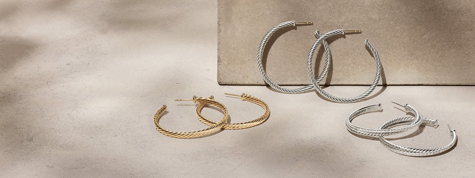 Three pairs of David Yurman Cable Classics Collection® hoop earrings in 18K yellow gold or sterling silver scattered on a light pink textured stone with long shadows.