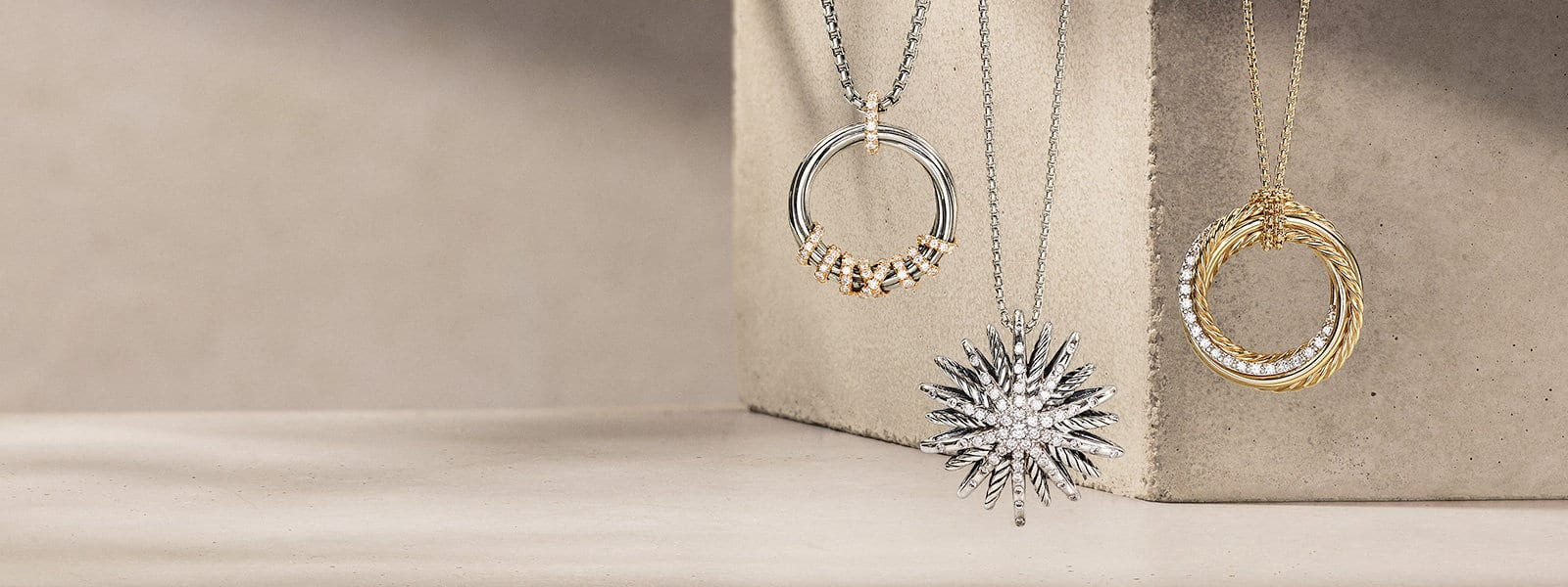 David Yurman Helena, Starburst and Crossover pendant necklaces in sterling silver with 18K yellow gold with pavé diamonds, sterling silver with pavé diamonds or 18K yellow gold with pavé diamonds hanging above a light pink textured stone with long shadows.