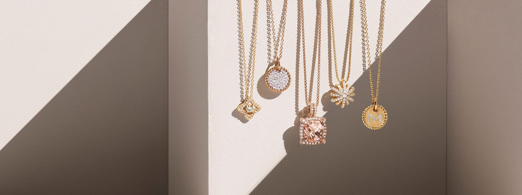 "A color photo shows five David Yurman pendant necklaces for women from the Venetian Quatrefoil, Châtelaine, Starburst and Cable Collectibles collections hanging in front of a beige-hued stone backdrop with hard diagonal shadows. The necklaces are crafted from 18K yellow gold with white diamonds and circular, quatrefoil- or star-shaped pendants. Third from the left is a Châtelaine necklace with a cushion-shaped morganite pendant and a pavé white diamond bezel. Fifth from left is a Cable Collectibles necklace with a circular initial charm featuring a pavé diamond ""M"" and a ring of Cable."