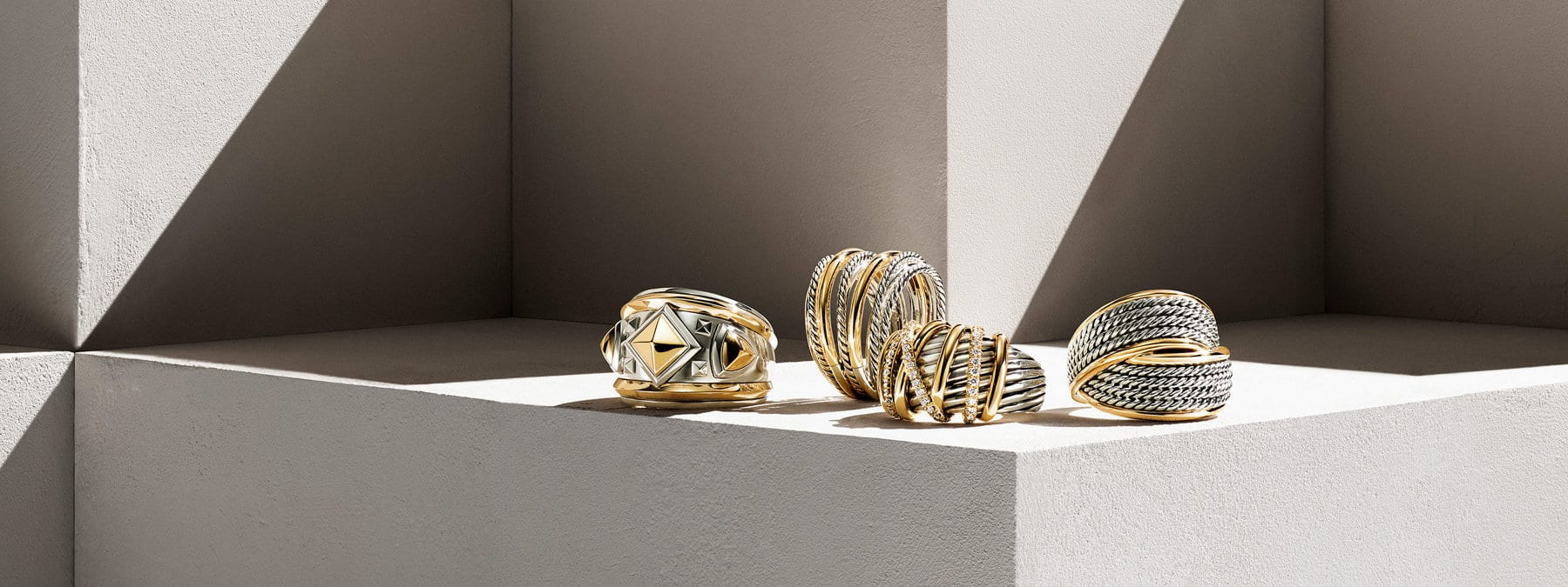 A color photograph shows four David Yurman rings from the Bold Renaissance, Crossover, Helena and DY Origami collections atop a beige-hued stone shelf with hard diagonal shadows. The women's rings are crafted from sterling silver with 18K yellow gold details. The third ring from the left features threads of pavé white diamonds.