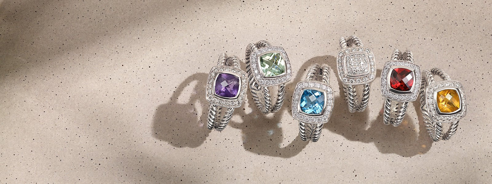 David Yurman Châtelaine® rings in sterling silver with diamonds or colored gemstones scattered on a light pink textured stone with long shadows.