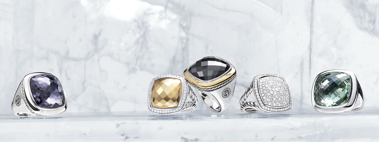 Albion rings in sterling silver with black orchid (lavender amethyst over hematine), bonded gold dome and pavé white diamonds, 18K yellow gold and black onyx, mosaic pavé white diamonds or prasiolite, in a row on ice.