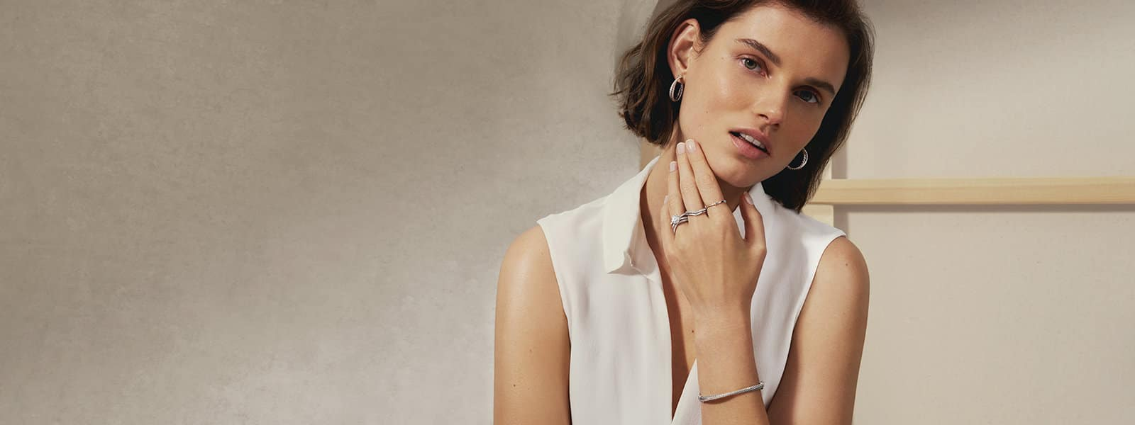 A model, wearing a white sleeveless blouse and David Yurman The Crossover Collection® and wedding designs in sterling silver or 18K white gold with white diamonds, standing in front of stone and wood surfaces.