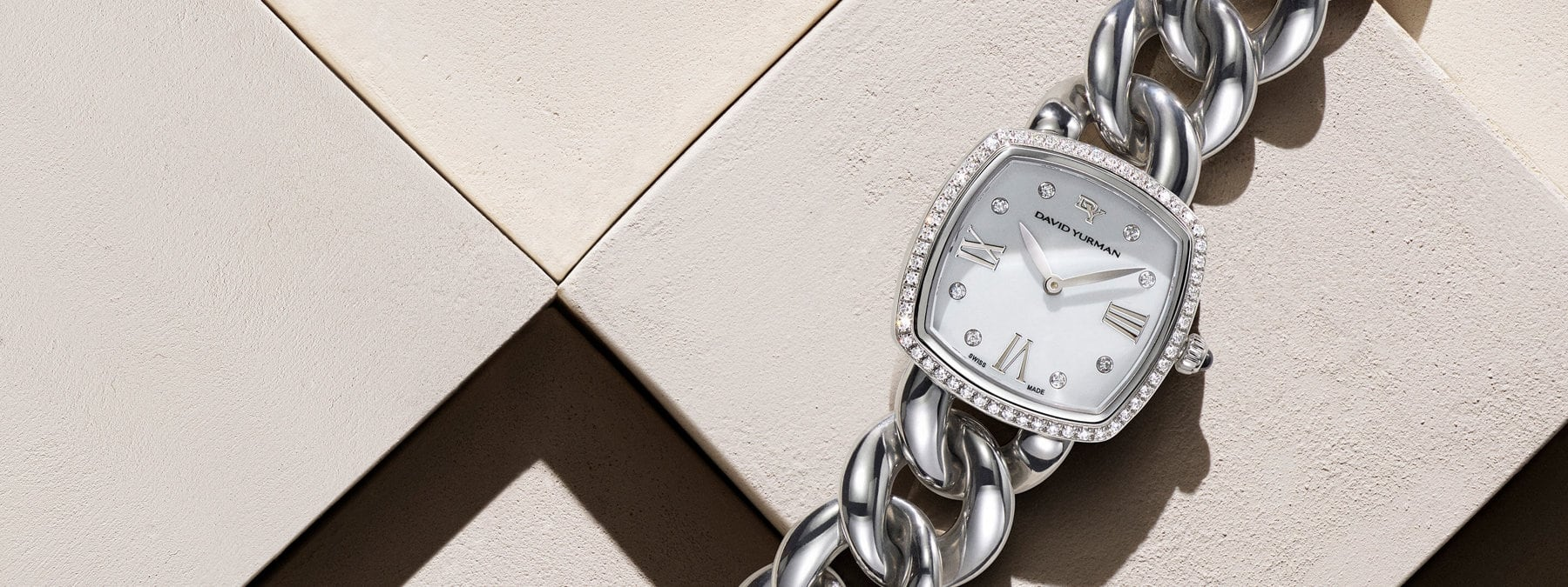 A color photograph shows a close-up of a David Yurman Classic women's watch atop a beige-hued stone backdrop with hard diagonal shadows. The bracelet watch is crafted from stainless steel with a ring of pavé diamonds around its mother-of-pearl face and six white diamonds set between roman numerals on its face.