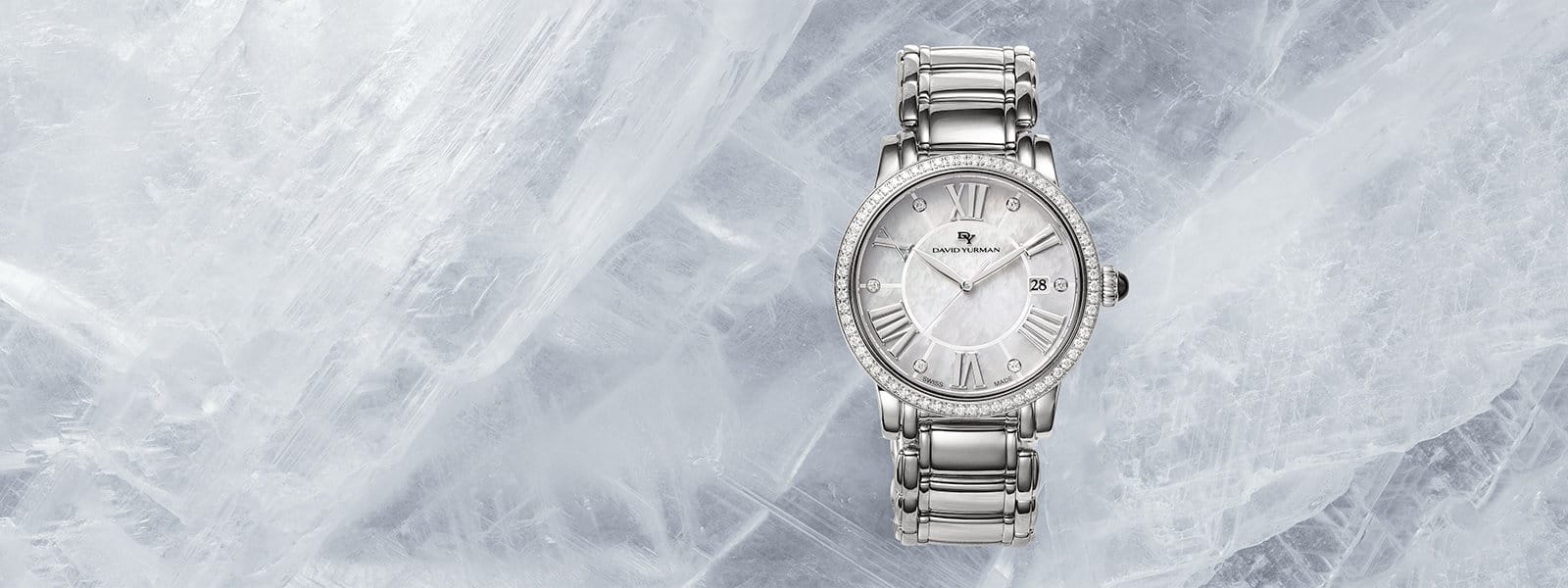 An overhead view of a Classic 30mm Quartz watch in stainless steel with a pavé white diamond bezel and a mother-of-pearl watch face, on a sheet of scratched ice.