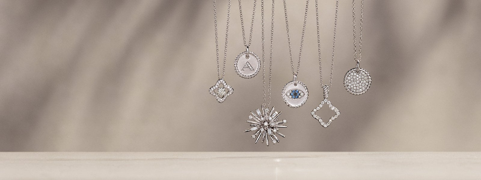 In 18K white gold with pavé diamonds and sapphires, five David Yurman charm necklaces from the Venetian Quatrefoil Collection, Supernova and Cable Collectibles hang in front of and above beige-colored stone surfaces with long shadows.