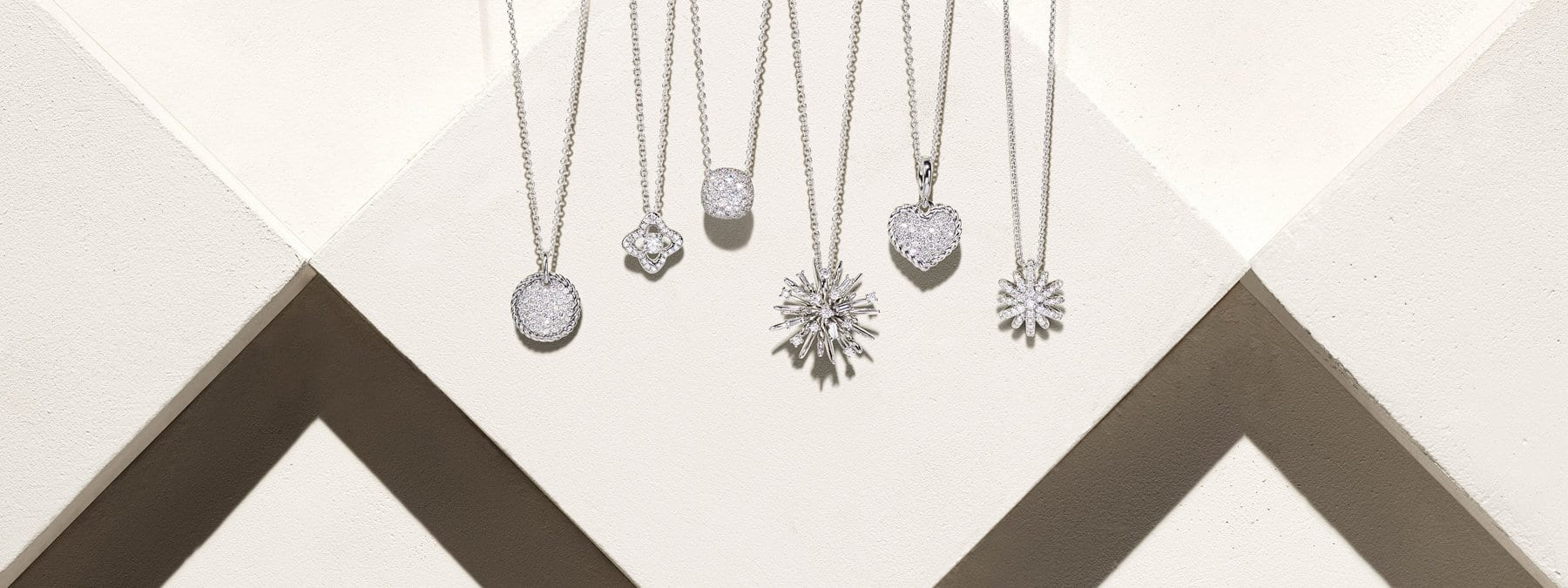 A color photo shows six David Yurman pendant necklaces for women from the Cable Collectibles, Venetian Quatrefoil, Châtelaine, Albion, Supernova and Starburst collections hanging in front of a beige-hued stone backdrop with hard diagonal shadows. The necklaces are crafted from 18K white gold with white diamond-encrusted circular, quatrefoil-, cushion-, heart- or star-shaped pendants.