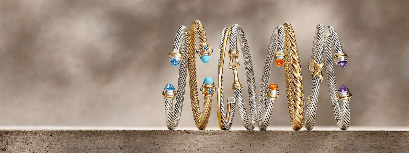 A horizontal stack of David Yurman The Cable Collection®, X Collection , Pure Form and Cable Loop bracelets in 18K yellow gold or sterling silver with or without diamonds, 14K yellow gold or colored gemstones on a beige textured stone with long shadows.