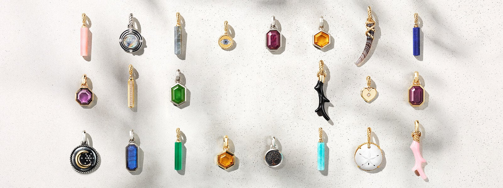 A horizontal grid of 22 amulet charms, in sterling silver or 18K yellow gold with a variety of different colored gemstones, on a white textured stone background with dark shadows.