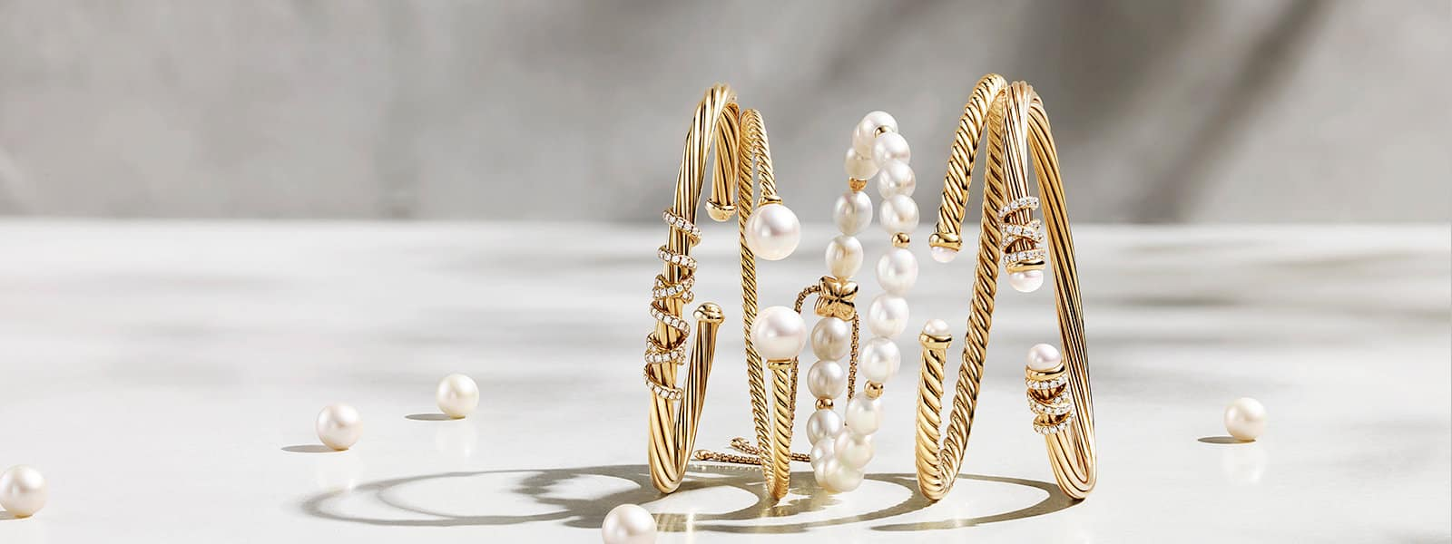 A horizontal stack of five David Yurman bracelets in 18K yellow gold with pavé diamonds and cultured pearls on a white-colored stone surface with loose pearls.