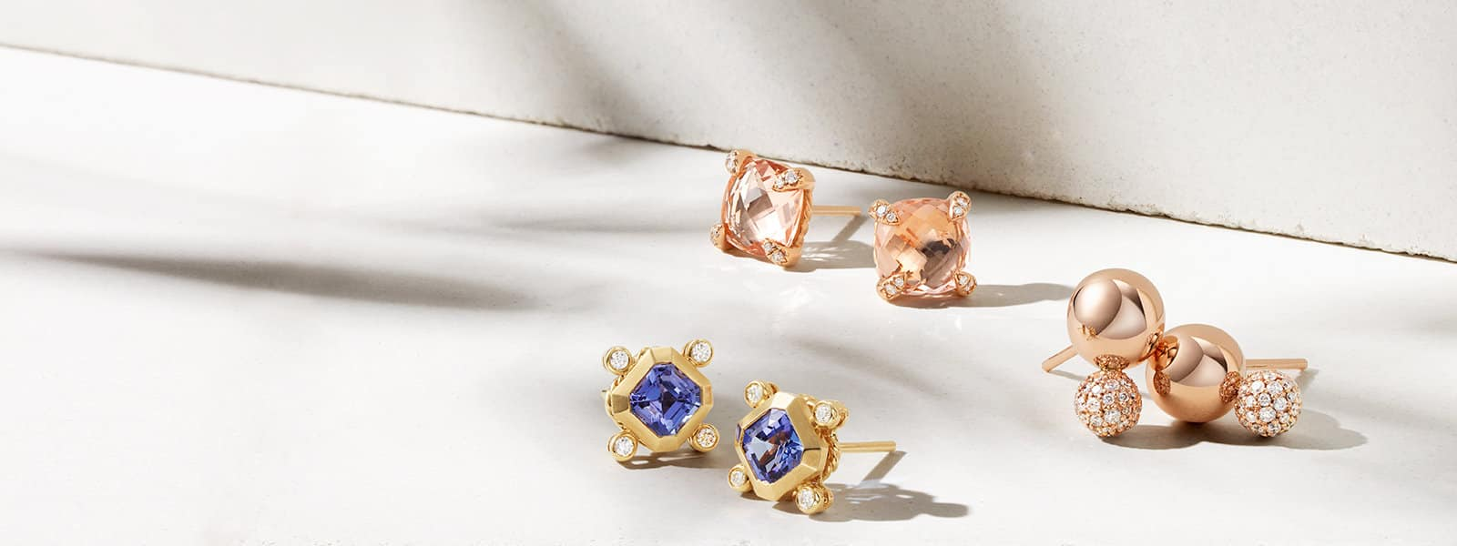 Three pairs of David Yurman Novella, Châtelaine and Solari stud earrings in 18K yellow gold or 18K rose gold with blue topaz, pavé diamonds, morganite, all scattered on a light pink textured stone with long shadows.
