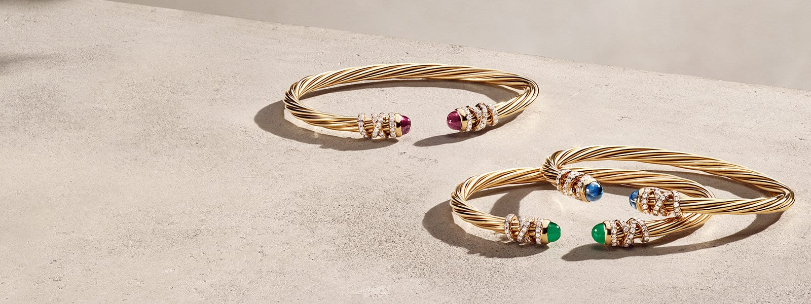 Three David Yurman Helena bracelets in 18K yellow gold with pavé diamond strands wrapped near the ruby, emerald and light blue sapphire end caps—all scattered on a light pink textured stone.