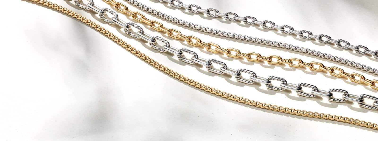 Diagonal rows of five David Yurman chain necklaces in sterling silver or 18K yellow gold on a white textured stone with long shadows.