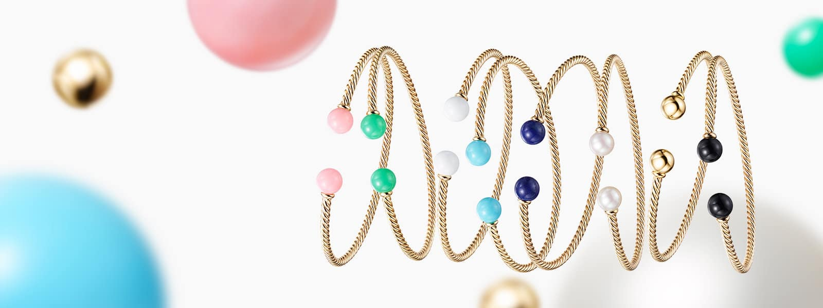 A horizontal stack of six David Yurman Solari bracelets in 18K yellow gold with colored gemstones, all suspended above large spheres of colored gemstones on a white background.