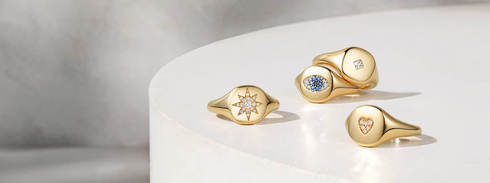 Four David Yurman pinky rings in 18K yellow gold with a pavé diamond star, diamond, heart and evil eye with sapphires, all scattered on a white circular stone surface.