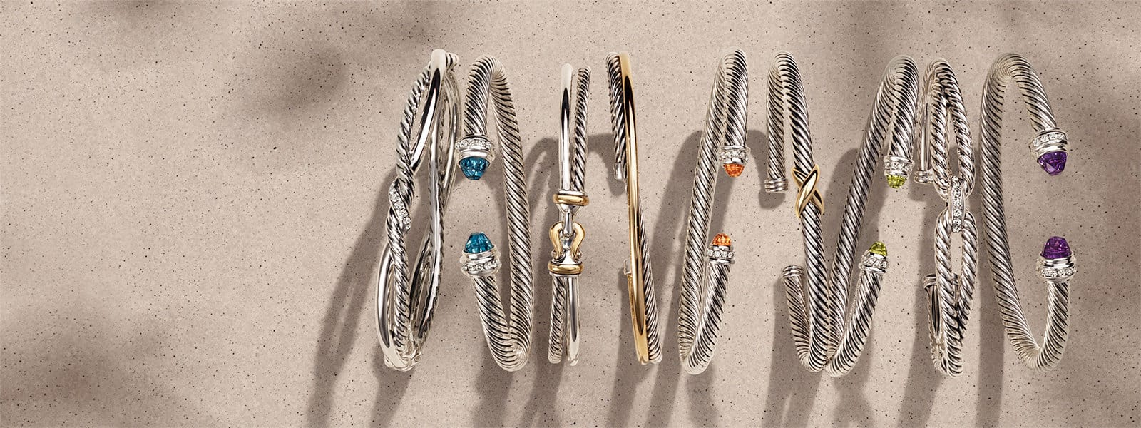 A horizontal stack of nine David Yurman Continuance, The Cable Collection®, X Collection and the Cable Loop bracelets in sterling silver with or without diamonds, 14K yellow gold or colored gemstones on a beige textured stone with long shadows.