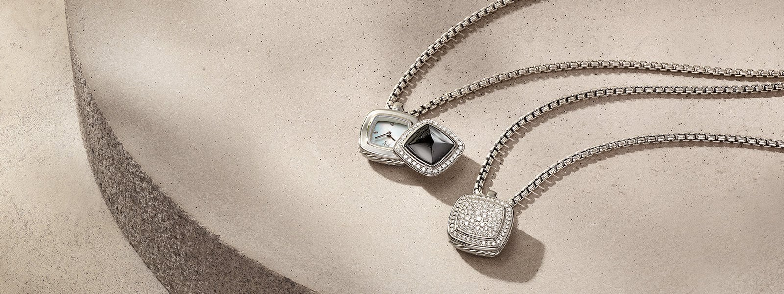 David Yurman Albion® pendant watches in sterling silver with stainless steel, black onyx and pavé diamonds lying on a round pink textured stone with shadows. One pendant watch's cover is open to reveal a clock face.