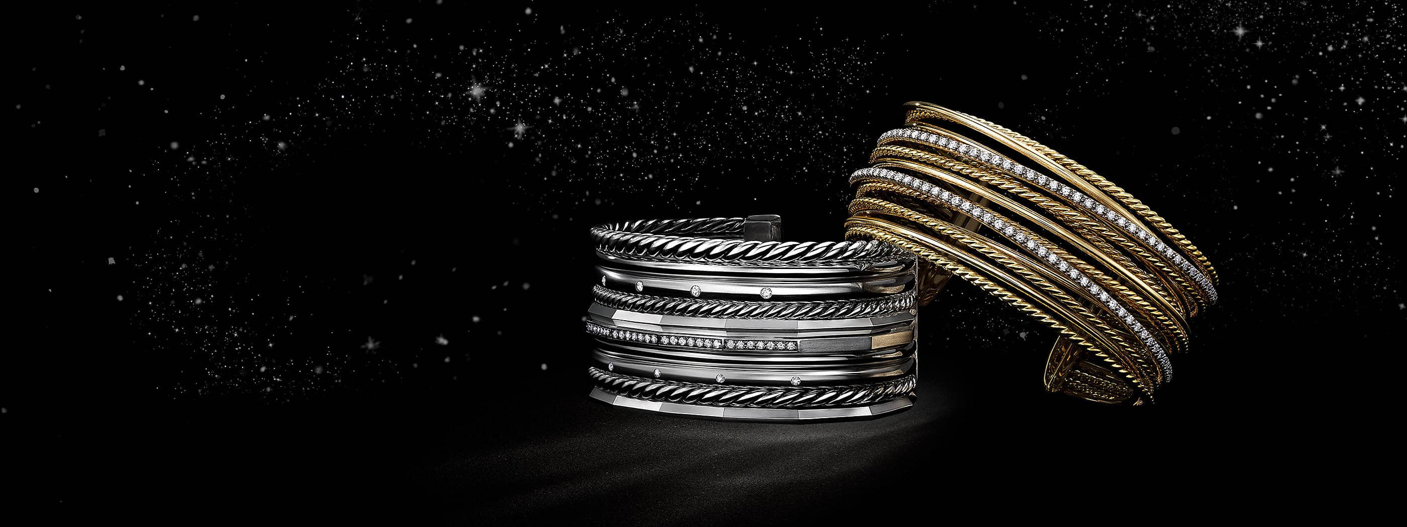 A color photograph shows two David Yurman women's cuff bracelets from the Stax and Crossover collections floating in front of a starry night sky. The bracelets are crafted from sterling silver Cable strands with pavé diamonds.
