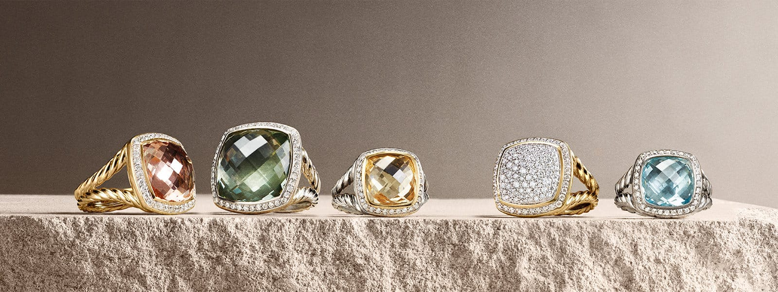 Albion® rings in 18K yellow gold and sterling silver with pavé diamonds and colored gemstones on a stone.