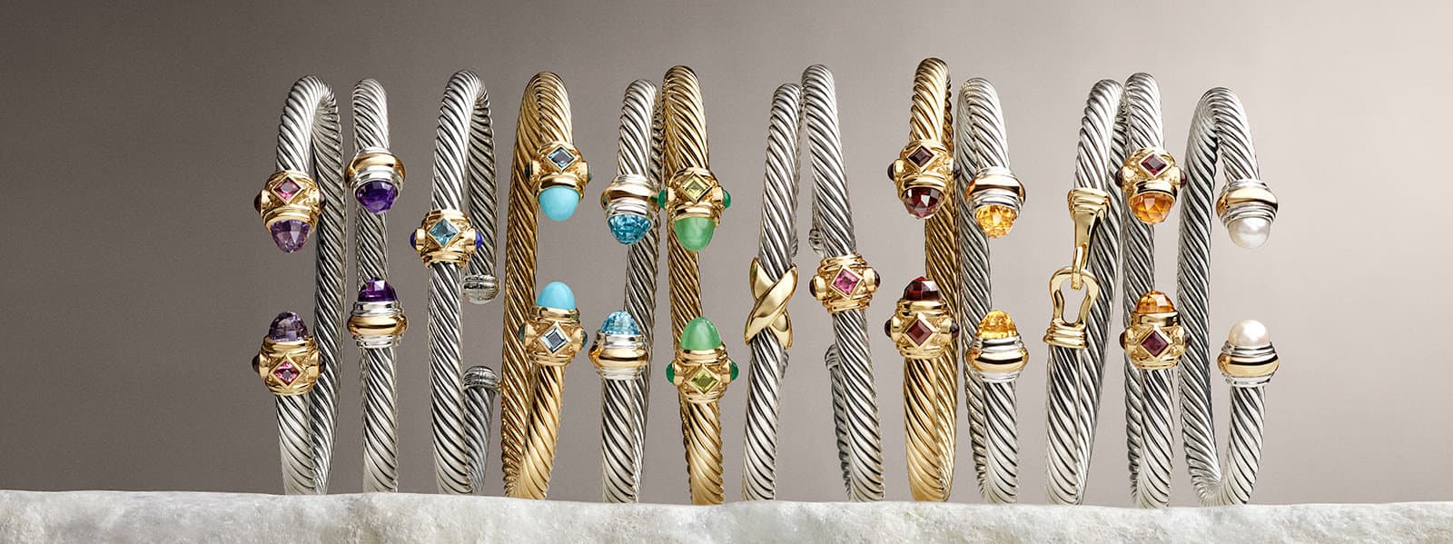 Cable Buckle Collection® and Cable Classics Collection® bracelets in sterling silver with 18K yellow gold, blue topaz and turquoise on a white stone.