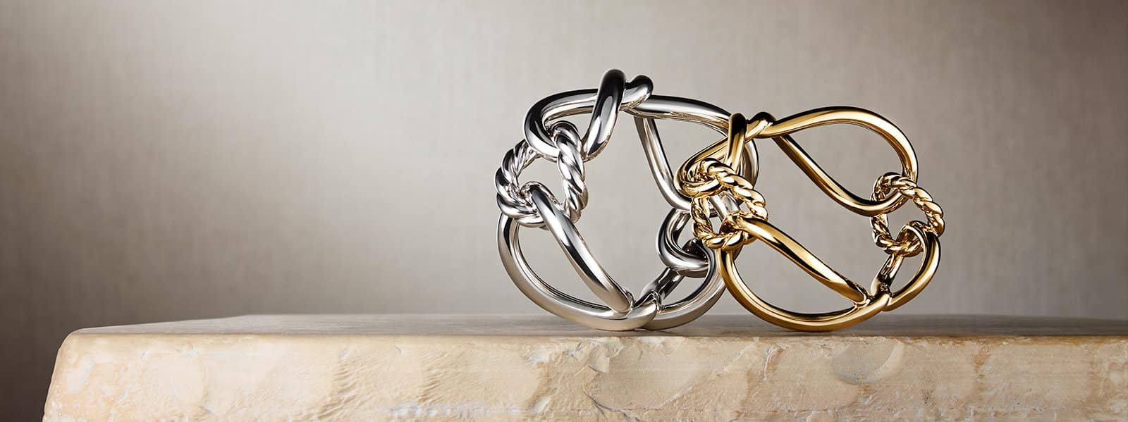Continuance® bracelets in sterling silver and 18K yellow gold on a stone.