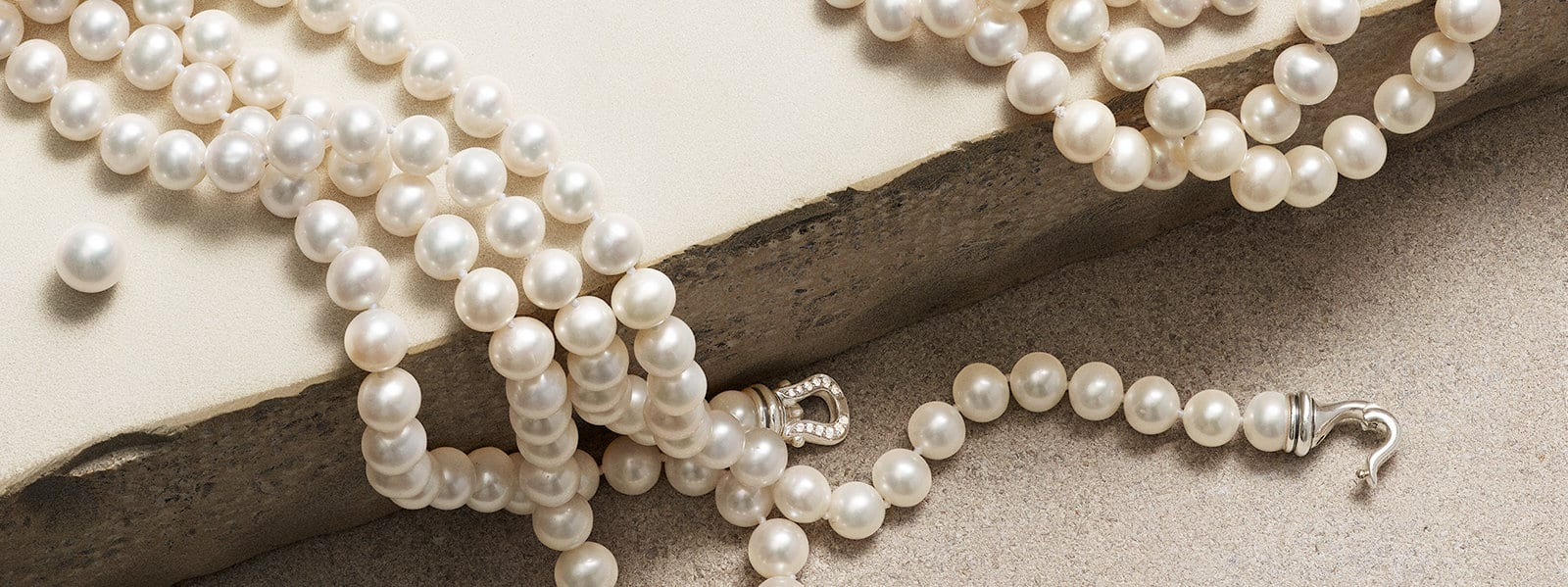 A pearl necklace with a diamond-encrusted sterling silver buckle on a stone.