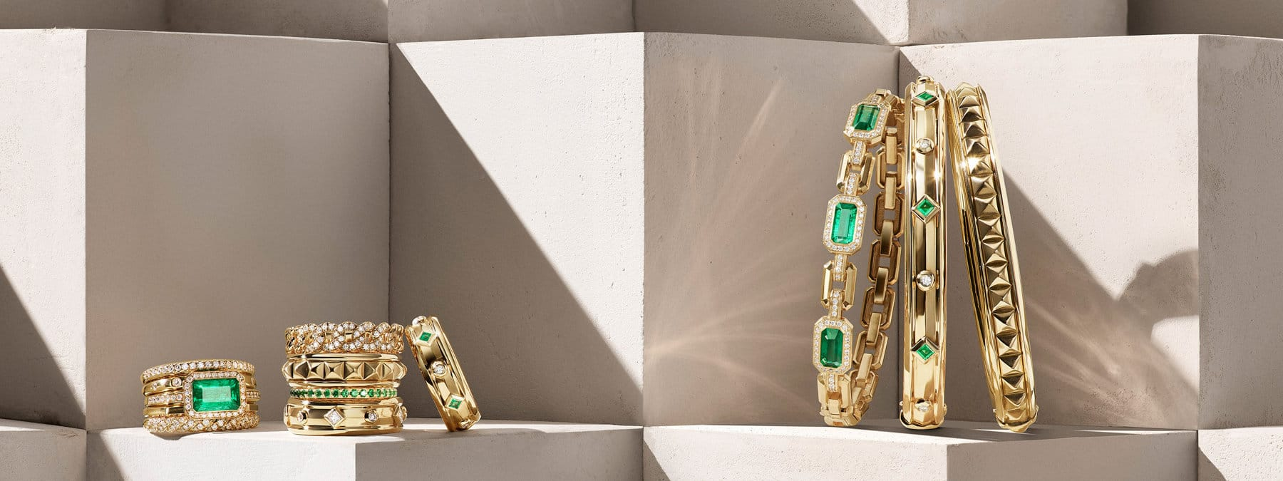 A color photo shows six David Yurman rings from the Stax, Belmont, Modern Renaissance and DY Eden collections on a stone shelf near a horizontal stack of David Yurman Novella and Modern Renaissance bracelets. The jewelry is crafted from 18K yellow gold with or without diamonds, emeralds and tsavorites. In the background are diagonal shadows and reflections of light.