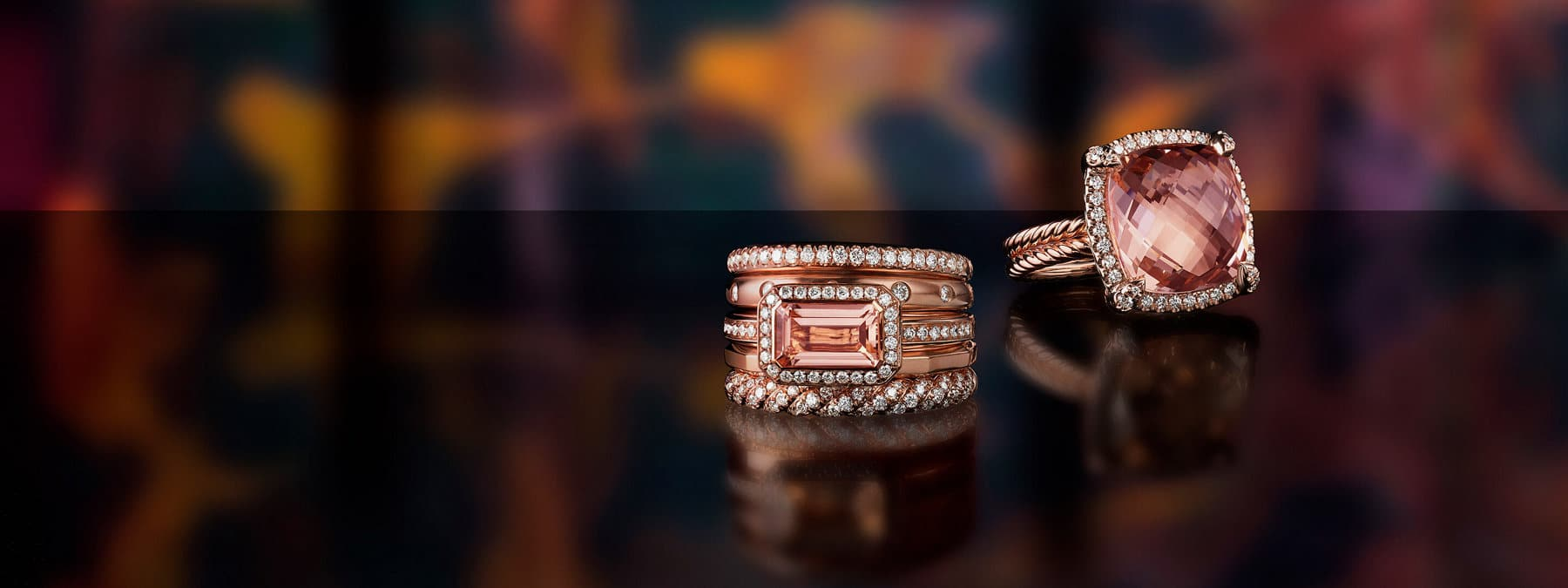 A color photograph shows a David Yurman Stax five-row ring and a Châtelaine ring scattered on a black reflective surface with a colorful stained glass panel illuminated behind them. The women's rings are crafted from 18K rose gold with pavé diamonds and morganite.