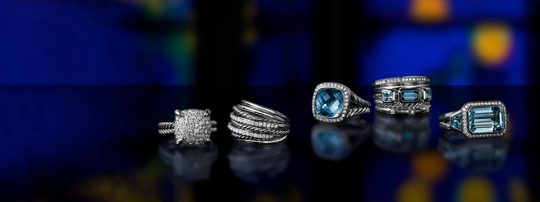 A color photograph shows five David Yurman rings from the Châtelaine, Crossover, Albion, Stax and Novella collections scattered on a black reflective surface with a colorful stained glass panel illuminated behind them. The women's rings are crafted from sterling silver with pavé diamonds and with or without blue topazes.
