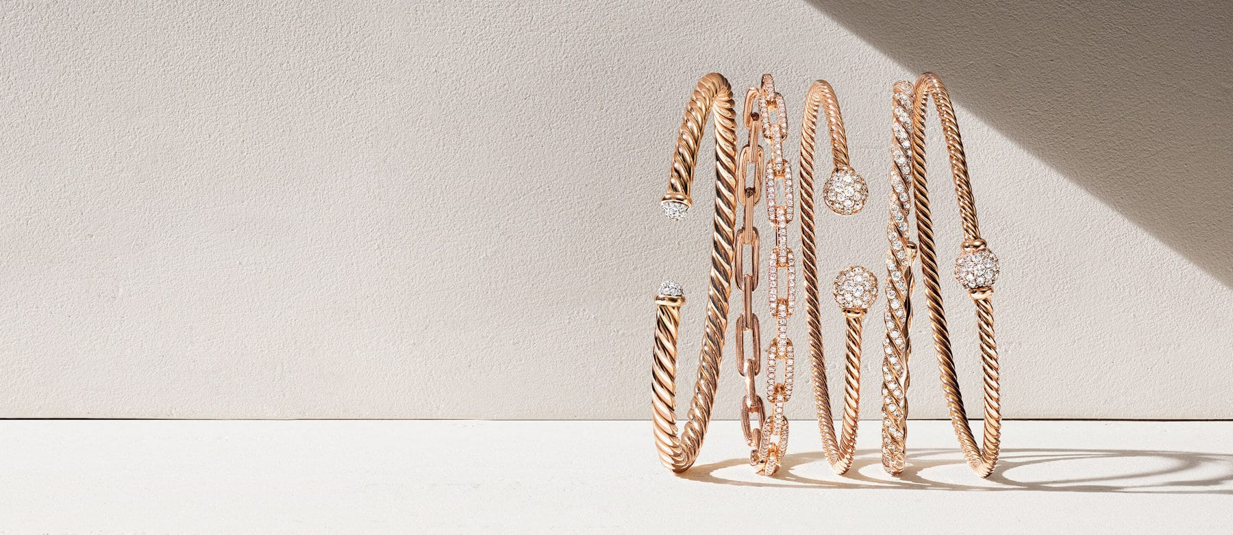 A color photograph shows five David Yurman rose gold-and-diamond bracelets from the Cable, Stax, Solari and Pavéflex collections atop a beige surface.