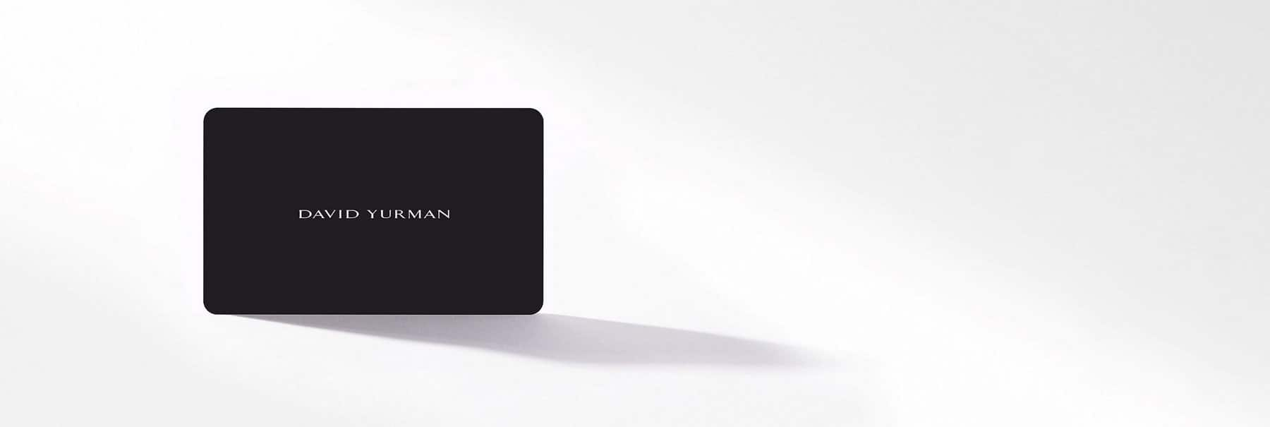 """A color photograph shows a grey """"David Yurman"""" gift card against a white background."""