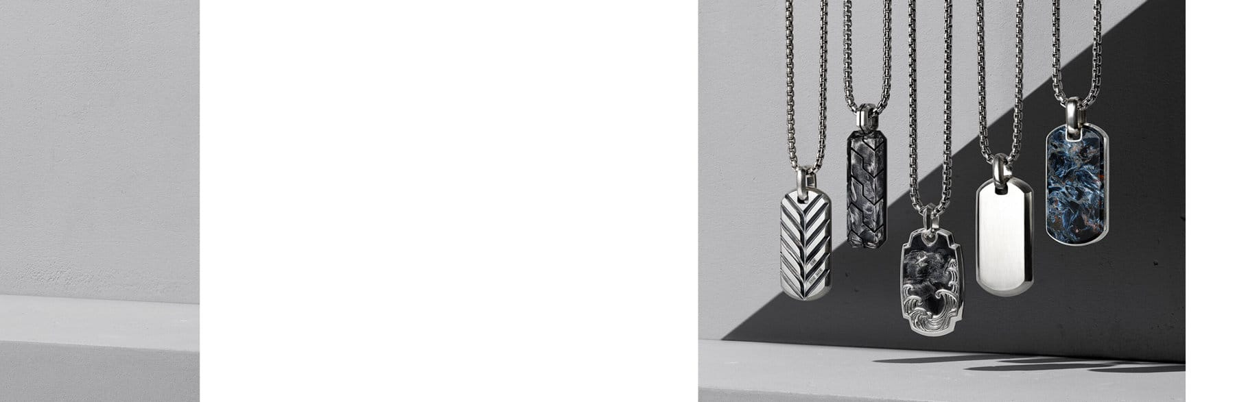 A color photograph shows a row of five David Yurman tags from the Streamline, Forged Carbon, Waves and Exotic Stone collections atop a grey background. Each is crafted from sterling silver with or without forged carbon or pietersite.