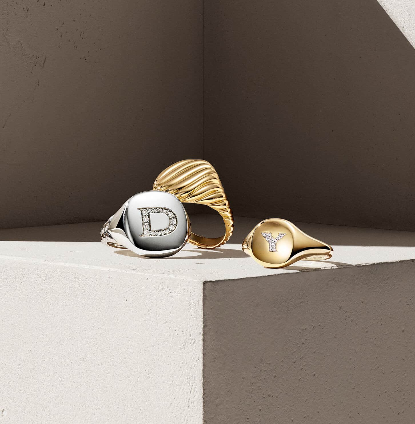 A color photograph shows three David Yurman Cable Collectibles pinky rings atop a beige surface. Each ring is crafted from sterling silver or 18K yellow gold with or without diamonds.