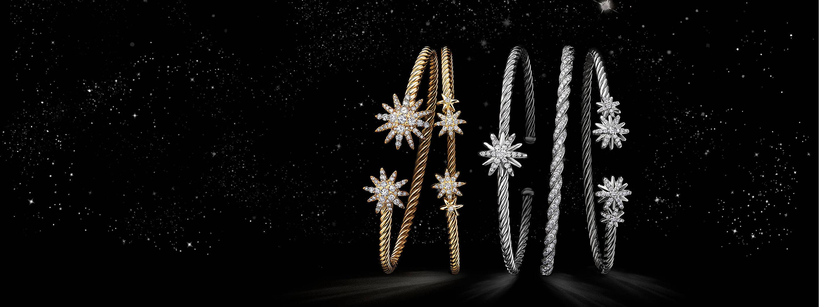 A color photograph shows a horizontal stack of five David Yurman women's bracelets from the Starburst and Pavéflex collections floating in a starry night sky. The jewelry is crafted from 18K white or yellow gold with pavé diamonds or sterling silver with pavé diamonds.