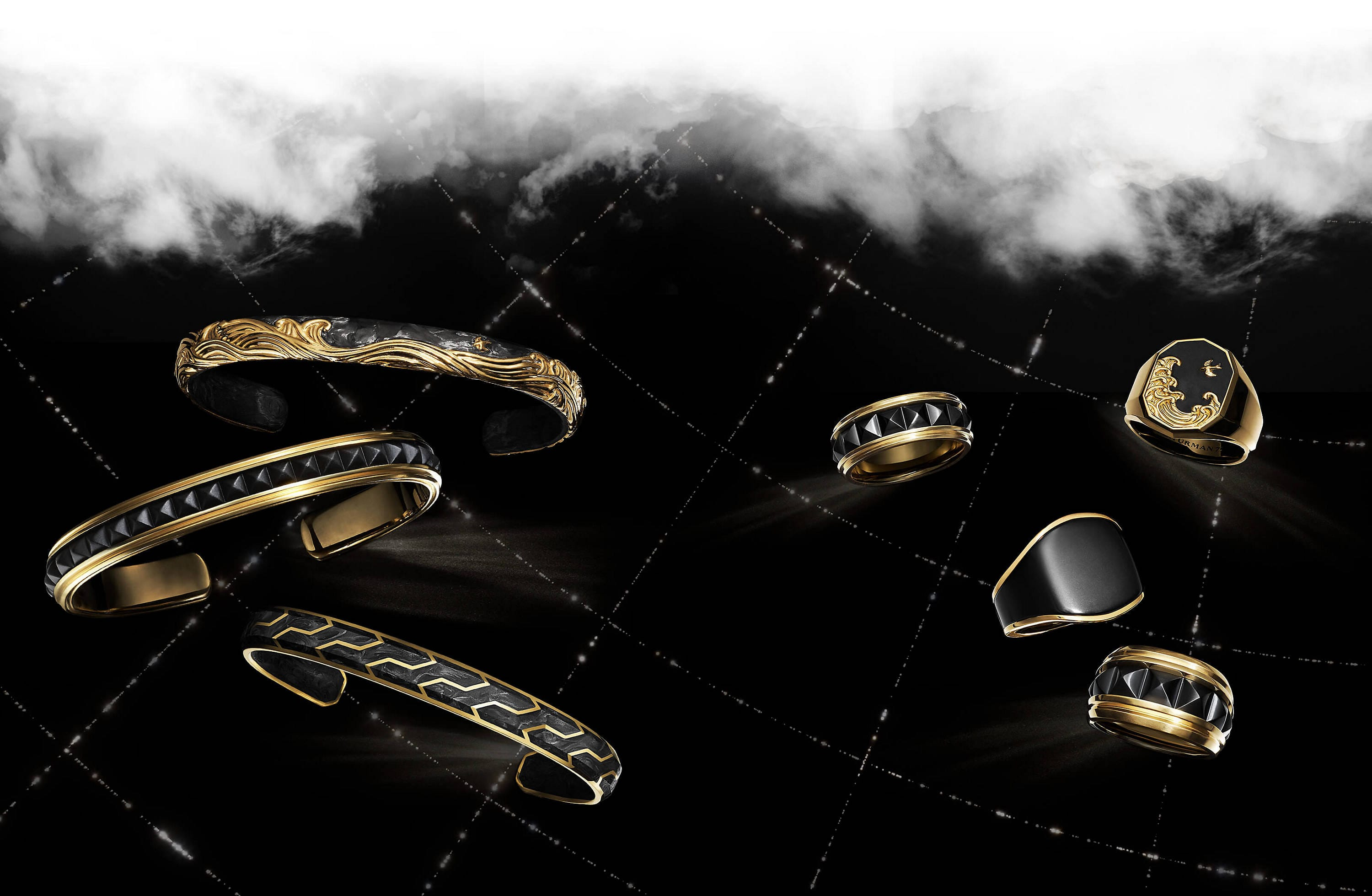 A color photo shows three David Yurman men's bracelets and four men's rings floating in a night sky with white clouds, and latitude and longitude lines. The jewelry is crafted from 18K yellow gold with or without forged carbon or black titanium.