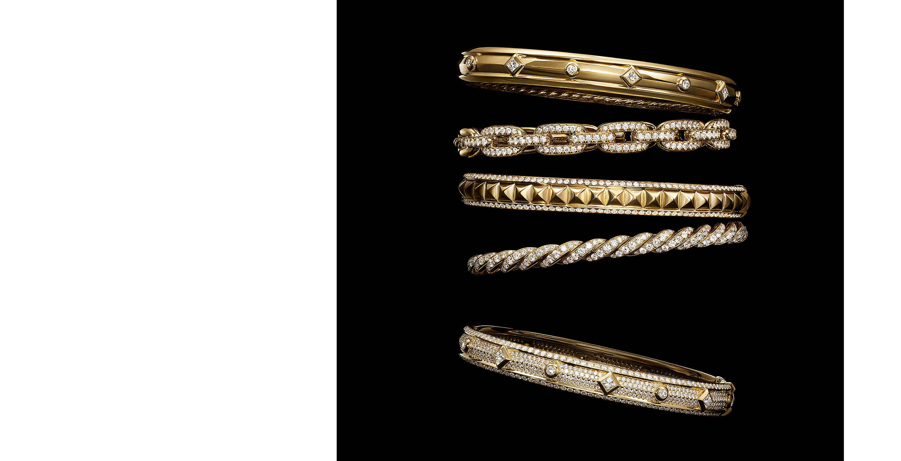 A color photo shows a vertical stack of four David Yurman women's bracelets from the Modern Renaissance, Stax and Pavéflex collections floating in front of a starry night sky. The jewelry is crafted from 18K yellow gold with diamonds