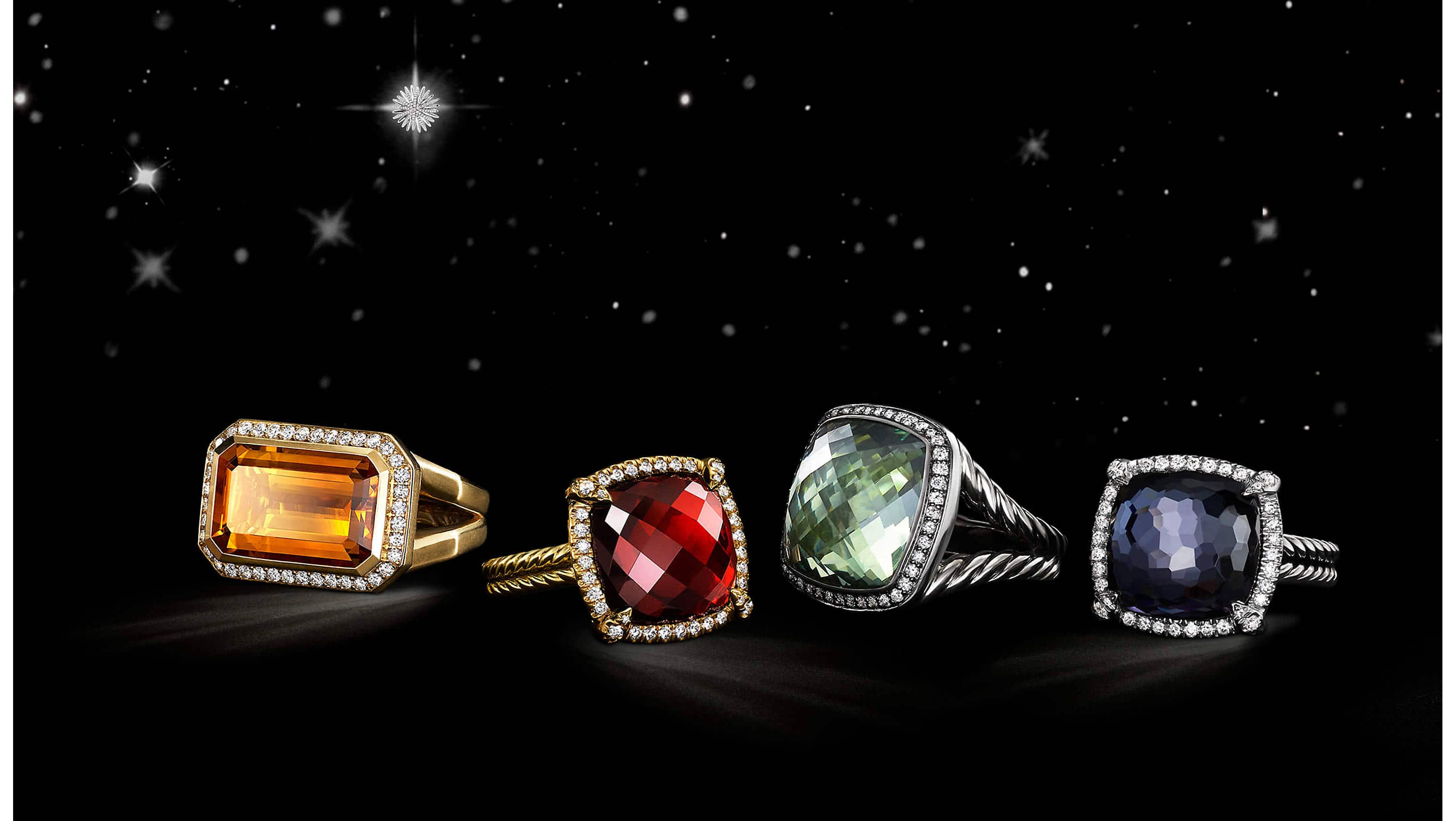 A color photo shows four David Yurman women's rings floating in a starry night sky with clouds. The rings are crafted from 18K yellow gold or sterling silver with pavé diamonds surrounding Madeira citrine, garnet, prasiolite or black orchid center stones.